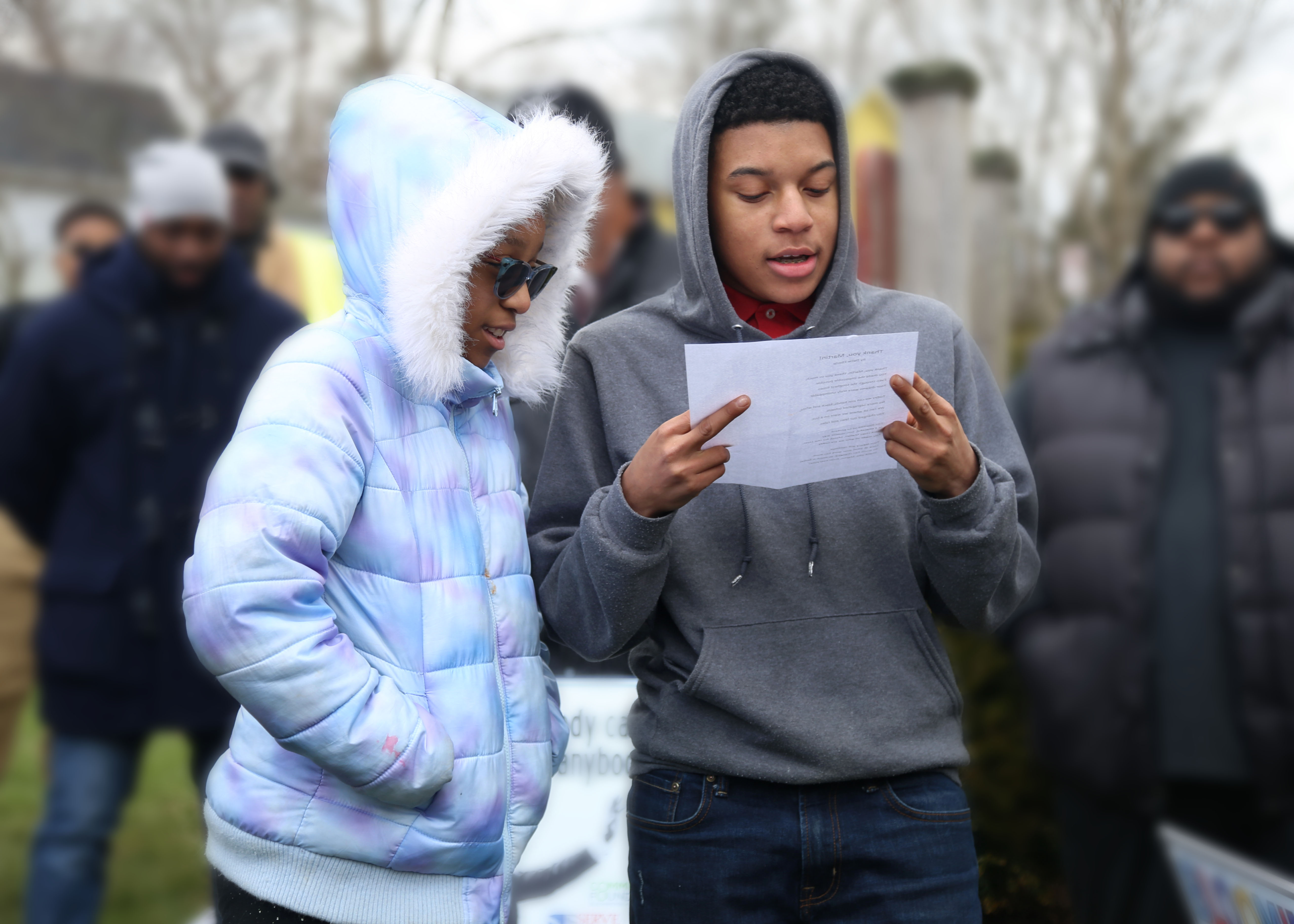 Student Shaun Wilson (right) reads a poem written by sixth-grade student Demaris Eberle (left) before the march.