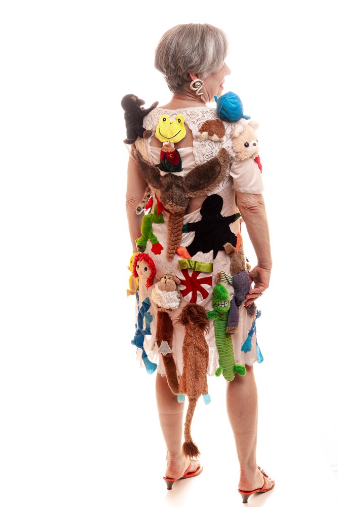 """Babe in Toyland"" created and modeled by Jane Matranga for Trashion. Deconstructed dog and children's toys festoon a pink nightdress with glittery fabric."