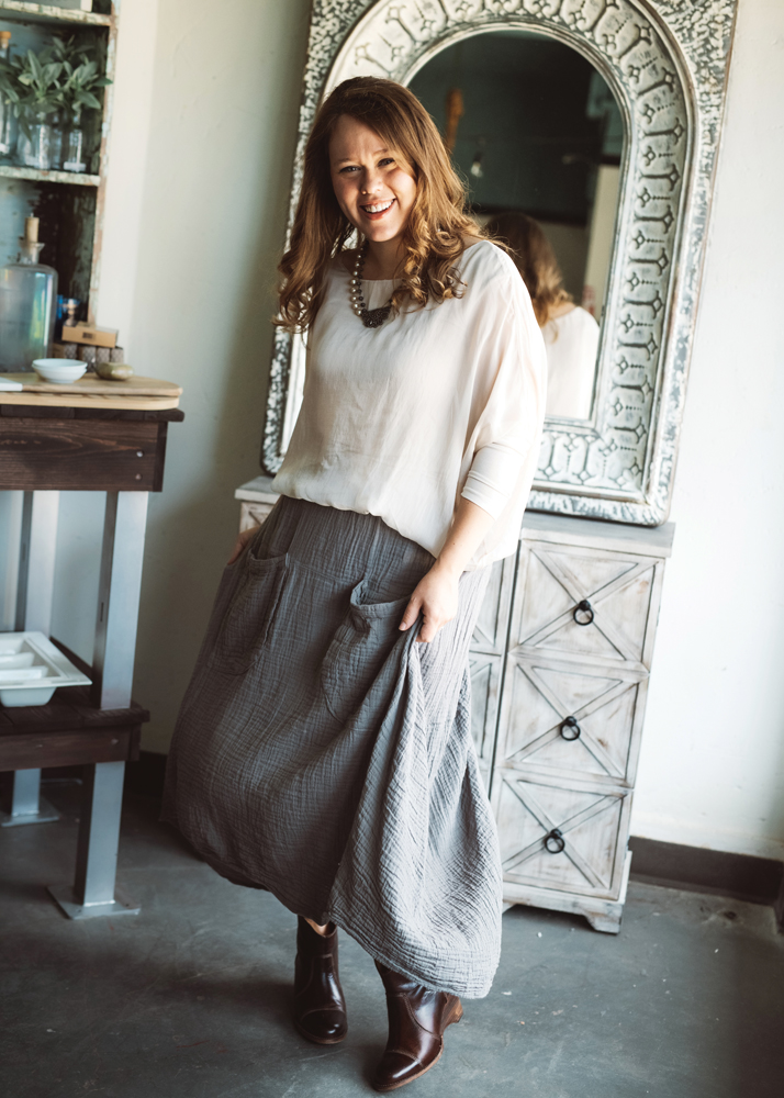 Amanda Calvert sports a pair of Bed Stu ankle boots in cognac with a champagne silk blouse and a gray cotton double-pocket skirt. Blouse by Cobblestone, skirt by Nusantara, and necklace by Lola + Company.
