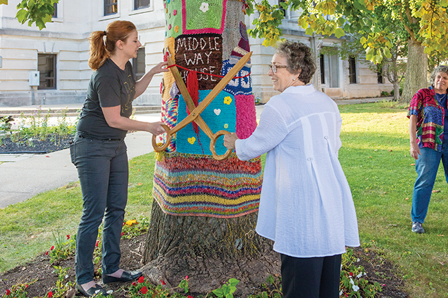"""Diane Neal (left) and Toby Strout cut the """"ribbon"""" on the Middle Way House Tree. Photo by James Kellar"""