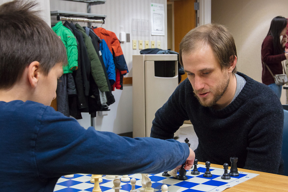 John Illg teaches strategy to a young chess club member. Photos by James Kellar